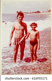 USSR, ABKHAZIA, LESELIDZE - CIRCA 1979: Vintage photo of dad with little daughter on Black sea beach in Abkhazia, USSR