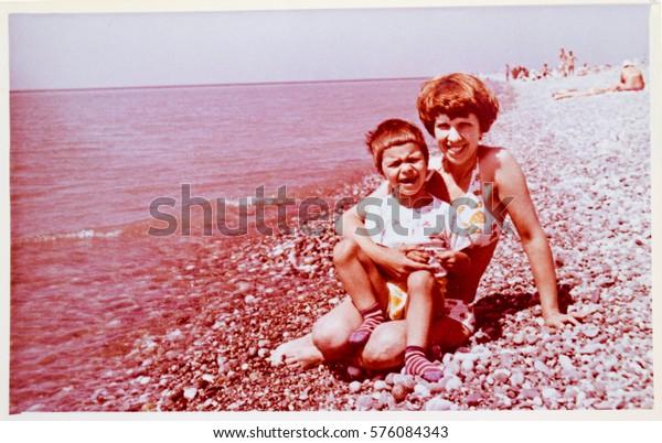 USSR, ABKHAZIA, LESELIDZE - CIRCA 1979: Vintage photo of mother with little son on Black Sea beach