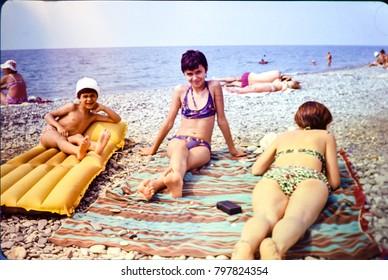 USSR, ABKHAZIA, LESELIDZE - CIRCA 1981: Vintage photo of family beach photo in Leselidze, Abkhazia, USSR