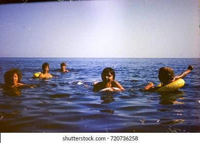 USSR, ABKHAZIA, LESELIDZE - CIRCA 1983: Vintage photo of family swimming in Black sea in Leselidze village, Abkhazia, USSR