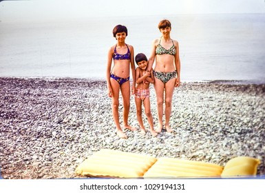 USSR, ABKHAZIA, LESELIDZE VILLAGE - CIRCA 1981: Vintage photo of young mom with kids beach family photo