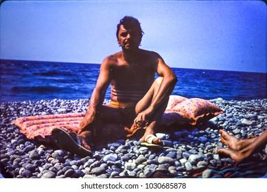 USSR, ABKHAZIA, LESELIDZE VILLAGE - CIRCA 1982: Vintage photo of man on Black sea beach in Abkhazia, USSR