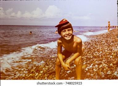 USSR, ABKHAZIA, LESELIDZE VILLAGE - CIRCA 1980: Vintage photo of little boy smiling pose on pebble Black sea beach in Leselidze, Abkhazia, USSR