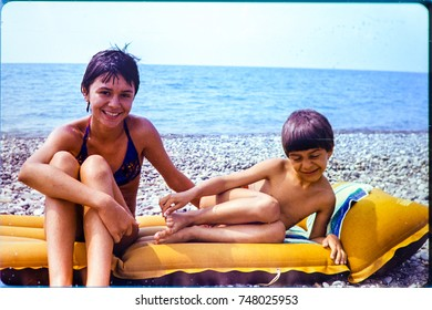 USSR, ABKHAZIA, LESELIDZE VILLAGE - CIRCA 1982: Vintage photo of sister with little brother beach scene portrait in Leselidze, Abkhazia, USSR