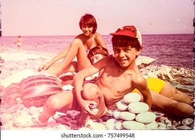 USSR, ABKHAZIA, LESELIDZE VILLAGE - CIRCA 1982: Vintage photo of mom with kids on pebble beach at Black sea, Abkhazia, USSR
