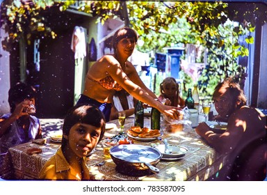 USSR, ABKHAZIA, LESELIDZE VILLAGE - CIRCA 1981: Vintage photo of group of people at table on summer vacation