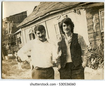 Ussr - CIRCA 1940s: An antique Black & White photo show Two men stand in the courtyard of his house
