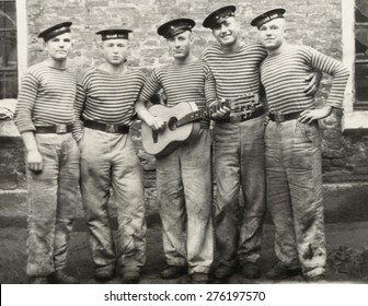 USSR - CIRCA 1950 s: The group of sailors in striped vests with a guitar, circa 1950s