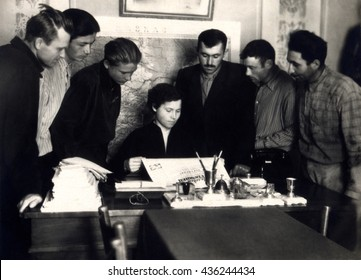 Ussr - CIRCA 1950s: An antique Black & White photo of  group of young men and woman reading newspaper in agitation room.
