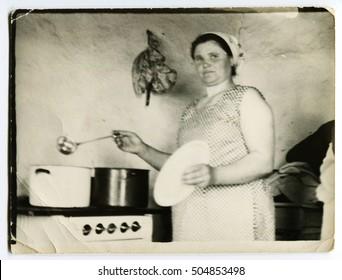 Ussr - CIRCA 1950s: An antique Black & White photo show Woman prepares soup