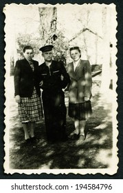 USSR - CIRCA 1950s: An antique photo shows sailor and two young women, USSR, circa 1950s