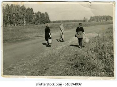 Ussr - CIRCA 1970s: An antique Black & White photo show Three women walk with buckets