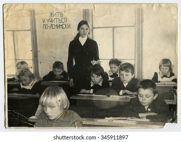 """USSR - CIRCA 1970s: An antique photo shows the teacher and the students, writing on the wall """"to learn to live on the Leninist"""", USSR, circa 1970s"""