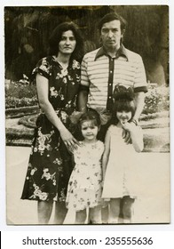 Ussr - CIRCA 1980s: An antique Black & White photo show family portrait: parents and two daughters, twins
