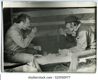 Ussr - CIRCA 1980s: An antique Black & White photo shows two men having lunch in the garage