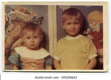 USSR - CIRCA 1980s: An antique photo shows brother and sister in the background of children's pictures, circa 1980s