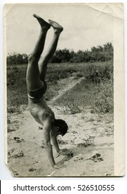 USSR - CIRCA 1980s : An antique photo show a young man walking on his hands on the beach