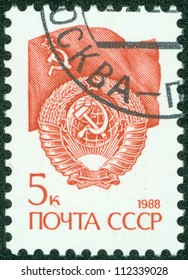 """USSR - CIRCA 1988: A stamp printed in USSR shows State Emblem and flag of the Soviet Union , series """"Emblem"""" , circa 1988"""