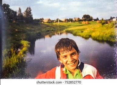 USSR, GDOV - CIRCA 1987: Vintage photo of boy smiling at village river landscape in Gdov, USSR