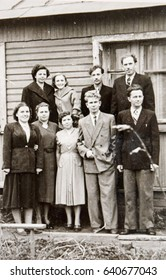 USSR, LENINGRAD, ALEXANDROVKA - CIRCA 1952: Vintage photo of young group of friends standing at rural house in Alexandrovka, Leningrad, USSR