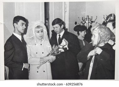 USSR, LENINGRAD - CIRCA 1969: Vintage photo of wedding couple with guests. Vintage photo of wedding couple. Just married couple. Soviet bride and groom wedding in Leningrad, USSR