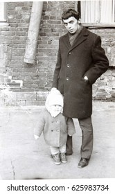 USSR, LENINGRAD - CIRCA 1970: Vintage photo of young father with little daughter walking in Leningrad, USSR