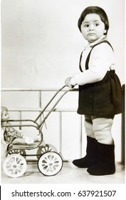USSR, LENINGRAD - CIRCA 1972: Vintage photo of little girl standing with toy baby stroller in Leningrad, USSR