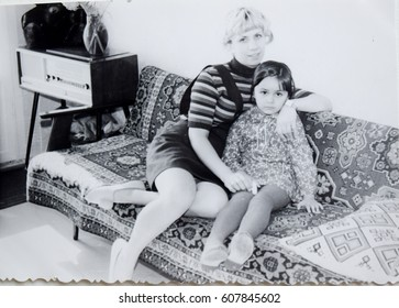 USSR, LENINGRAD - CIRCA 1973: Vintage photo of mom with daughter sitting on sofa in living room in Leningrad, USSR