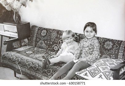 USSR, LENINGRAD - CIRCA 1973: Vintage photo of two little girls sitting on sofa in living room in Leningrad, USSR