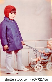 USSR, LENINGRAD - CIRCA 1973: Vintage photo of little girl standing with toy baby stroller with doll and smiling in Leningrad, USSR