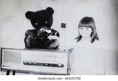 USSR, LENINGRAD - CIRCA 1973: Vintage photo of little girl at music player with teddy bear in Leningrad, USSR