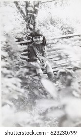 USSR, LENINGRAD - CIRCA 1974: Vintage photo of little girl smiling on summer garden bench Leningrad, USSR