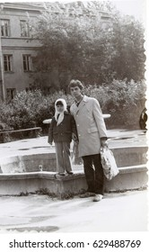 USSR, LENINGRAD  - CIRCA 1974: Vintage photo of young father with little daughter walking in Leningrad, USSR