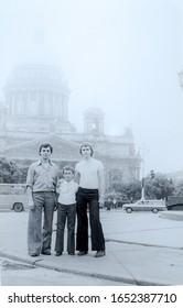 USSR, LENINGRAD - CIRCA 1976: Vintage photo of three brothers at Kazan Cathedral background in Leningrad, USSR