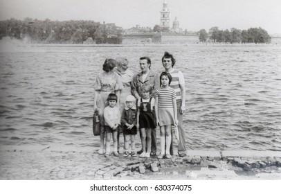 USSR, LENINGRAD - CIRCA 1978: Vintage photo of two families walk along Neva river embankment in Leningrad, USSR