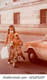 USSR, LENINGRAD - CIRCA 1980: Vintage photo of happy children on bicycle at red car in Leningrad, USSR