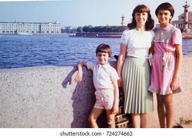USSR, LENINGRAD - CIRCA 1981: Vintage photo of mom with kids at walk on Neva river embankment in Leningrad, USSR