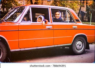 USSR, LENINGRAD - CIRCA 1981: Vintage photo of family car trip scene on autumn street in Leningrad, USSR