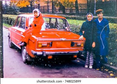 USSR, LENINGRAD - CIRCA 1982: Vintage photo of mom with kids at family soviet car Zhiguli Lada in autumn street in Leningrad, USSR
