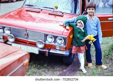 USSR, LENINGRAD - CIRCA 1982: Vintage photo of kids posing at family red car in Leningrad, USSR