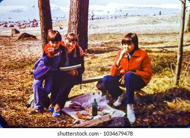 USSR, LENINGRAD - CIRCA 1983: Vintage photo of happy soviet family picnic scene on Finnish Gulf in Leningrad, USSR