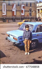 USSR, LENINGRAD - CIRCA 1985: Vintage photo of little boy standing at family blue Lada car on Pushkin square in Leningrad, USSR