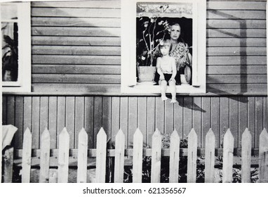 USSR, LENINGRAD, GORELOVO - CIRCA 1953: Vintage photo of young mother with little daughter in village house window in Leningrad, USSR