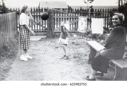 USSR, LENINGRAD, GORELOVO - CIRCA 1953: Vintage photo of little girl playing ball with mother and babysitter in Leningrad, Gorelovo, USSR