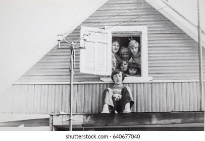 USSR, LENINGRAD, GORELOVO - CIRCA 1973: Vintage photo of group of young friends in attic window of rural house in Gorelovo, Leningrad, USSR