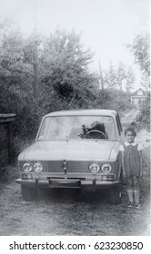 USSR, LENINGRAD, GORELOVO - CIRCA 1974: Vintage photo of little girl standing at own family car Zhiguli Lada in Leningrad, USSR