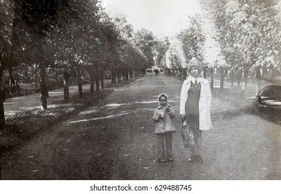 USSR, LENINGRAD, PETRODVORETS - now PETERHOF  - CIRCA 1973: Vintage photo of young mother with little daughter on Peterhof park alley in Leningrad, USSR