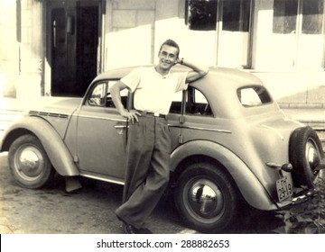 USSR, Russia, - CIRCA 1938: An antique black & white photo of young man standing near his car.