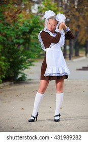 USSR school girl with white bows in park. The last bell and high school prom.