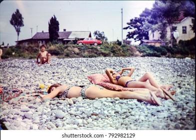 USSR, SOCHI - CIRCA 1982: Vintage photo of family beach scene on Black sea in USSR